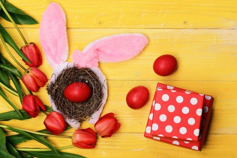 Groupe de fleurs près des oeufs dans le nid avec des oreilles de lapin photos libres de droits