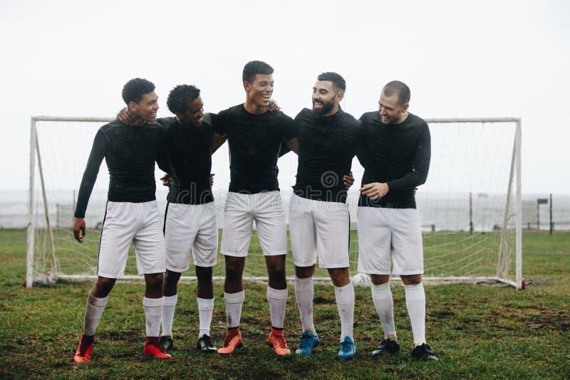 Groupe de footballeurs se tenant près du poteau images libres de droits