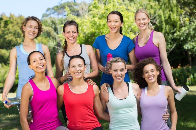 Groupe de forme physique souriant à l'appareil-photo en parc photos stock