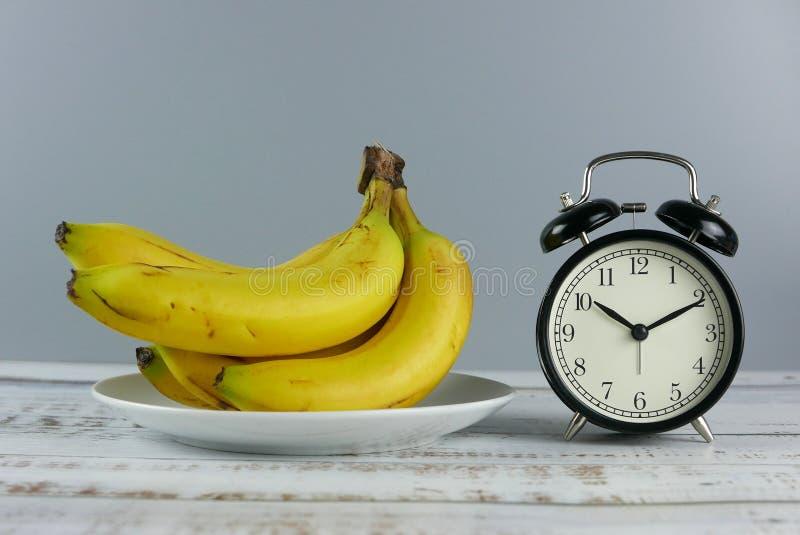 Groupe de foyer sélectif de bananes et d'exposition 10 d'horloge de table d'alarme après 10 o' ; horloge sur le fond en bois photographie stock libre de droits