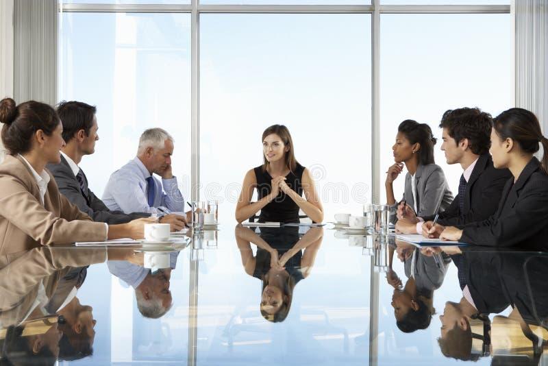 Groupe de gens d'affaires ayant la réunion du conseil d'administration autour du Tableau en verre photo stock