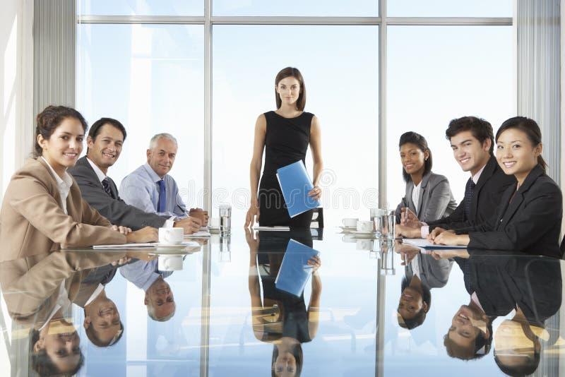 Groupe de gens d'affaires ayant la réunion du conseil d'administration autour du Tableau en verre images libres de droits