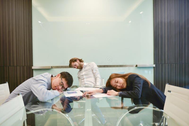 Groupe de gens d'affaires dormant dans le lieu de réunion avec la PIC vide photo libre de droits