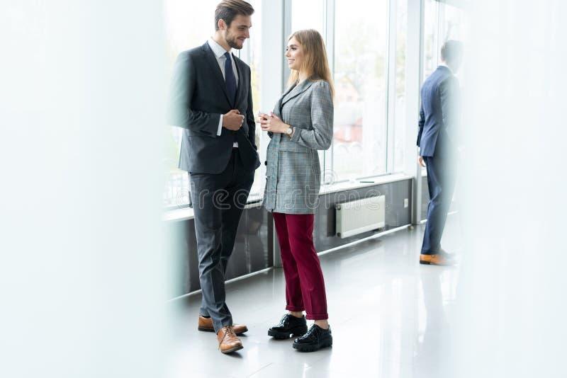 Groupe de gens d'affaires modernes causant pendant la pause-caf? se tenant dans le hall en verre ensoleill? de l'immeuble de bure images libres de droits