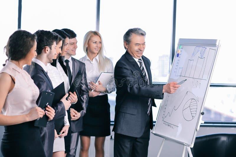 Groupe de gens d'affaires regardant le graphique sur le flipchart photographie stock libre de droits