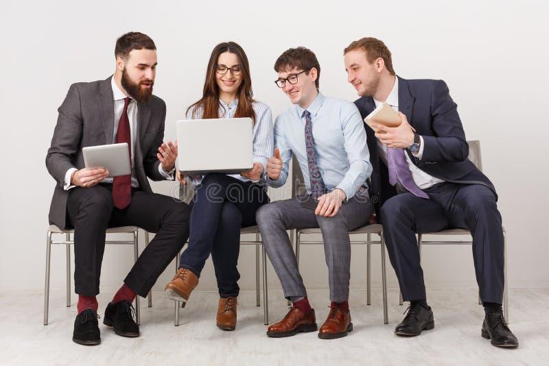 Groupe de gens d'affaires s'asseyant sur des présidences photographie stock libre de droits