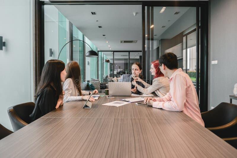Groupe de gens d'affaires se réunissant dans un lieu de réunion, partageant le thei photos libres de droits