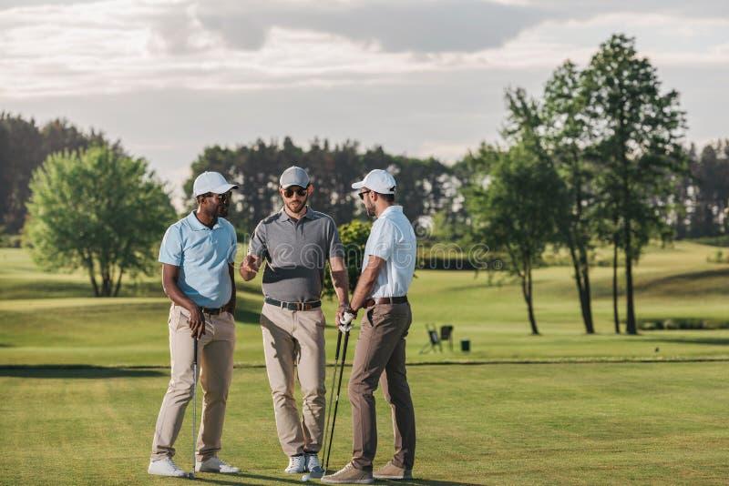 Groupe de golfeurs tenant des clubs et parlant tout en se tenant sur l'herbe verte images stock
