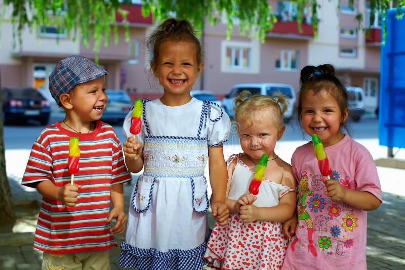 Groupe de gosses heureux mangeant la crême glacée de fruit photo libre de droits