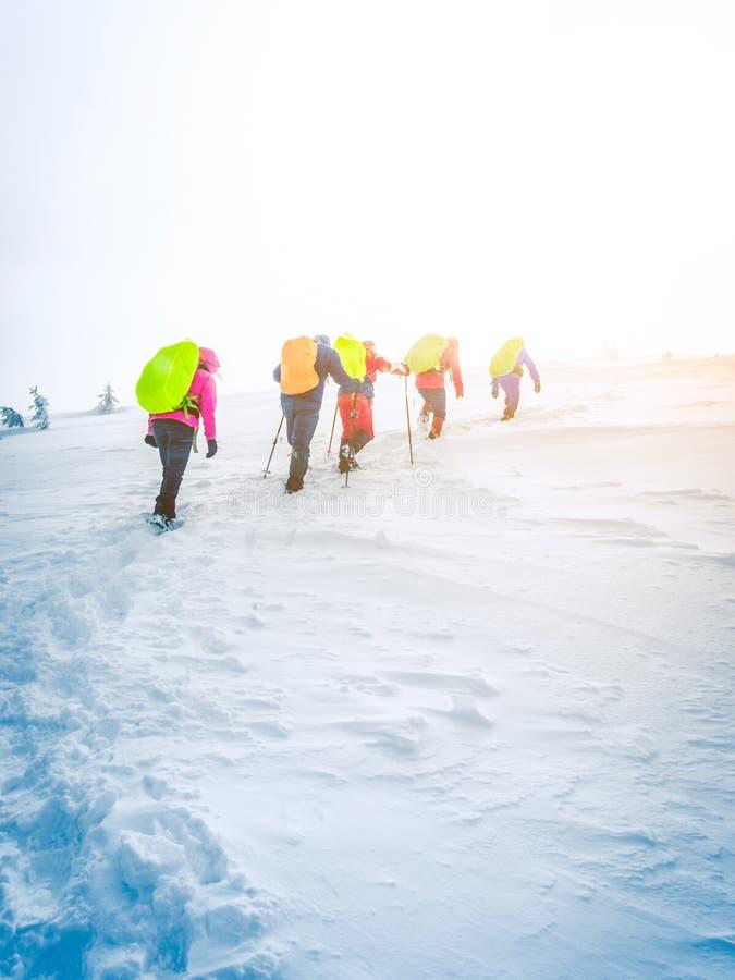 Groupe de grimpeurs allant au dessus de la montagne en hiver photo libre de droits