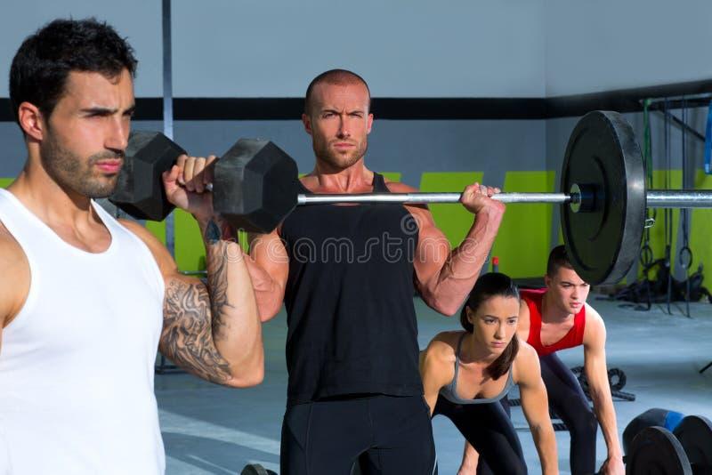 Groupe de gymnase avec la séance d'entraînement de crossfit de bar d'haltérophilie photo libre de droits