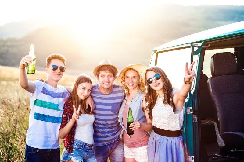 Groupe de hippies adolescents sur une promenade en voiture, bière potable photos libres de droits
