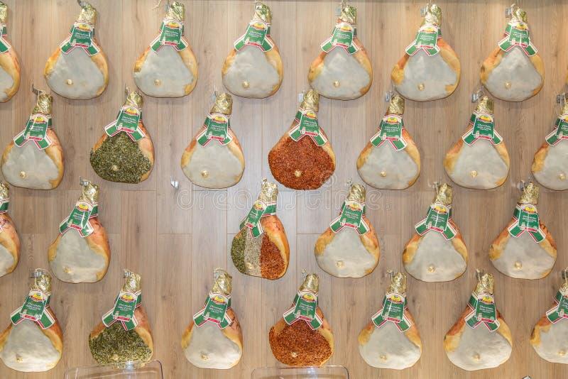 Groupe de jambons crus entiers accrochés sur un mur en bois photographie stock libre de droits