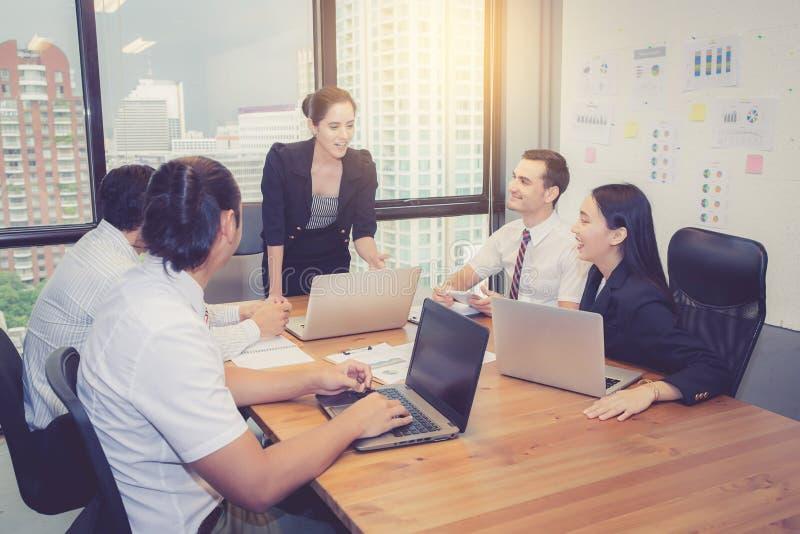 Groupe de jeune équipe d'affaires avec la réunion debout de chef de directeur de femme dans la salle de conférence images stock