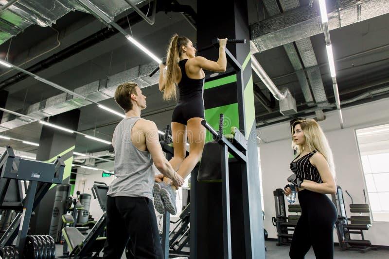 Groupe de jeune mâle trois attirant et d'adultes féminins dans le gymnase La jeune fille faisant la traction se lève sur la barre photos stock