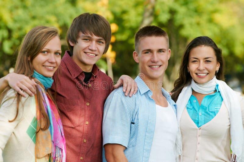 Groupe de jeunes étudiants de sourire à l'extérieur images stock