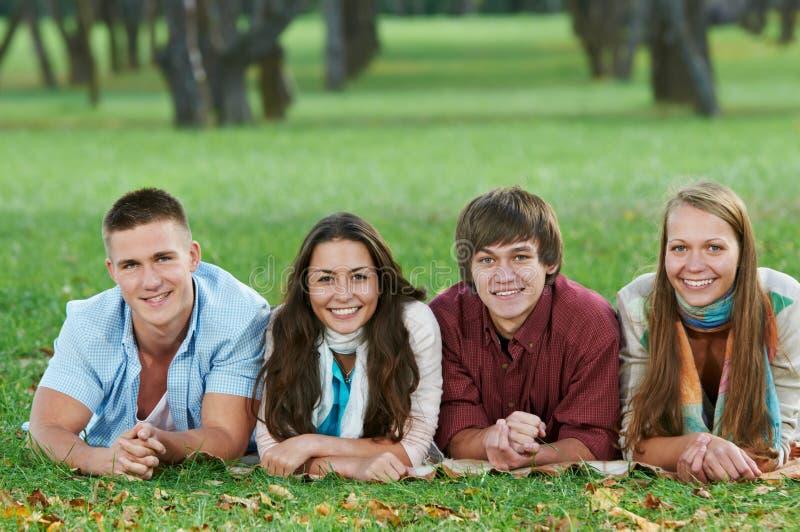 Groupe de jeunes étudiants de sourire à l'extérieur photos stock