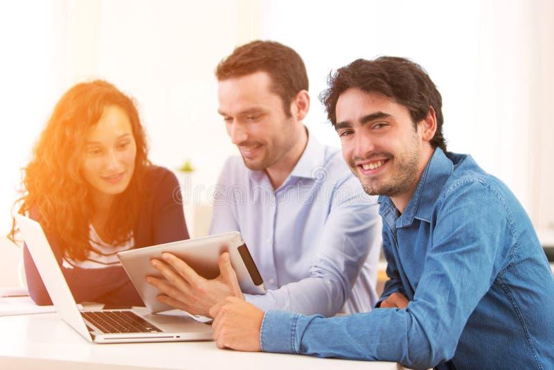 Groupe de jeunes actifs travaillant ensemble image stock