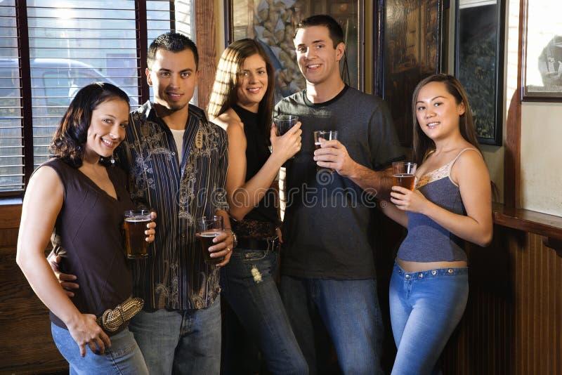 Groupe de jeunes adultes au bar. photographie stock libre de droits