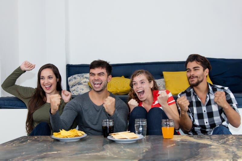 Groupe de jeunes adultes encourageant pour un but du football à la TV images libres de droits