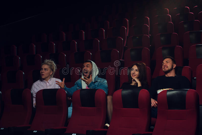 Groupe de jeunes adultes observant le film dans le théâtre photographie stock libre de droits