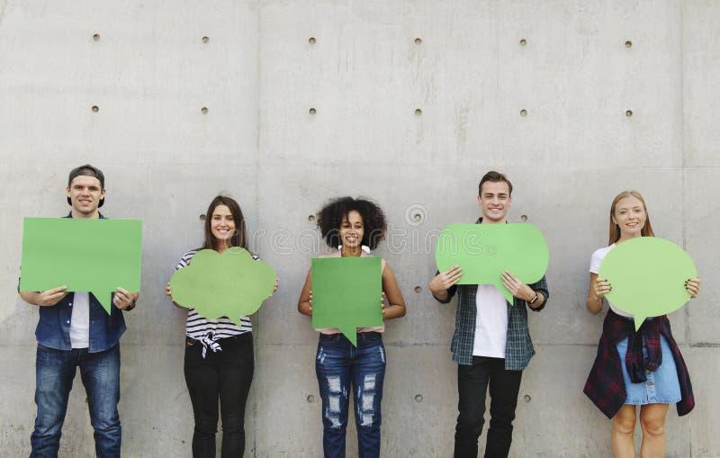 Groupe de jeunes adultes tenant dehors le copyspace vide t de plaquette photographie stock libre de droits