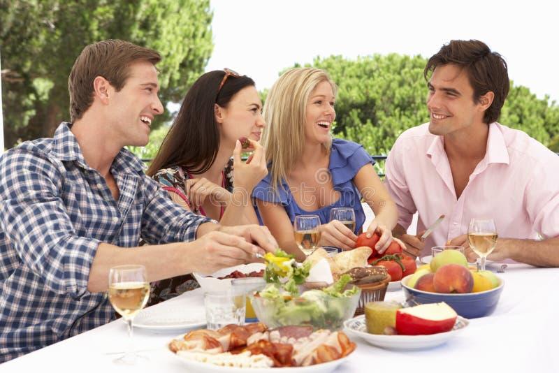 Groupe de jeunes amis appréciant le repas extérieur ensemble images stock