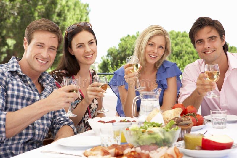 Groupe de jeunes amis appréciant le repas extérieur ensemble photographie stock