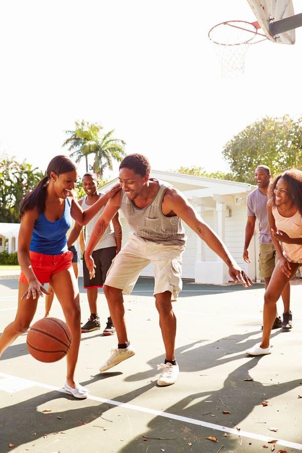 Groupe de jeunes amis jouant le match de basket photos stock