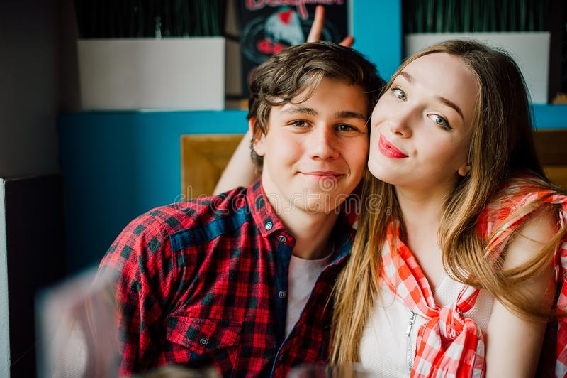 Groupe de jeunes amis traînant à un café Jeunes hommes et femmes se réunissant dans un café ayant l'amusement Mode de vie, amitié image stock