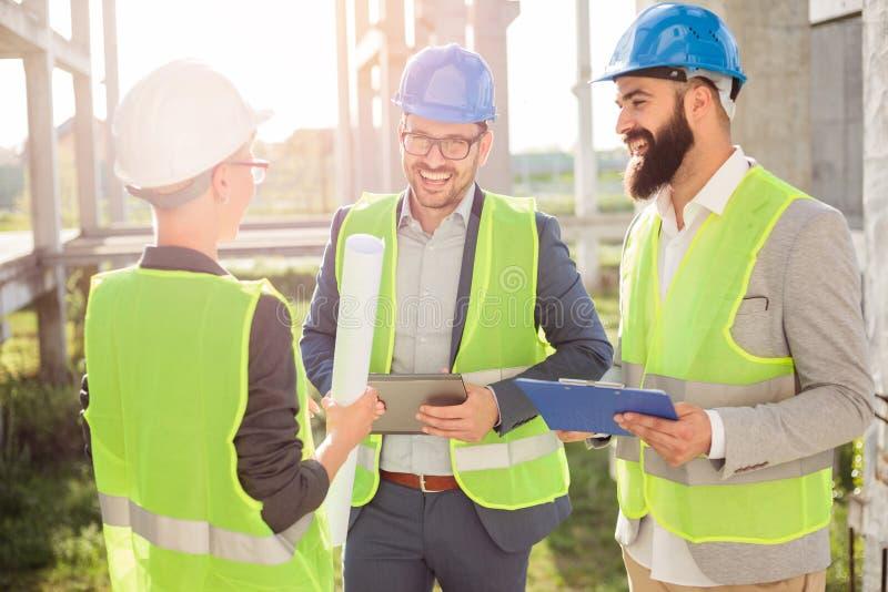Groupe de jeunes architectes ou associés se réunissant sur un chantier de construction photographie stock