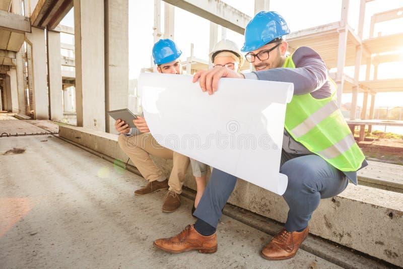 Groupe de jeunes architectes regardant des plans d'étage pendant l'inspection d'un chantier de construction photo stock