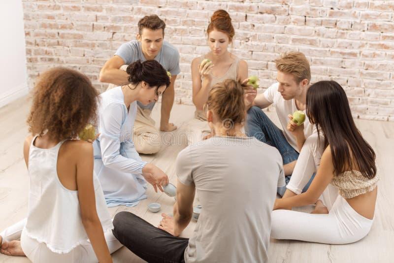 Groupe de jeunes beaux couples multi-ethniques se reposant ensemble et mangeant parlant de sourire photographie stock libre de droits