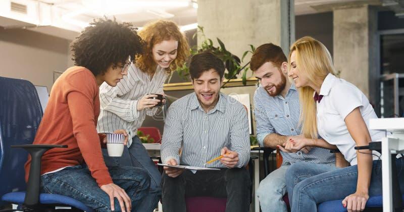 Groupe de jeunes coll?gues discutant la nouvelle strat?gie marketing dans le bureau image libre de droits