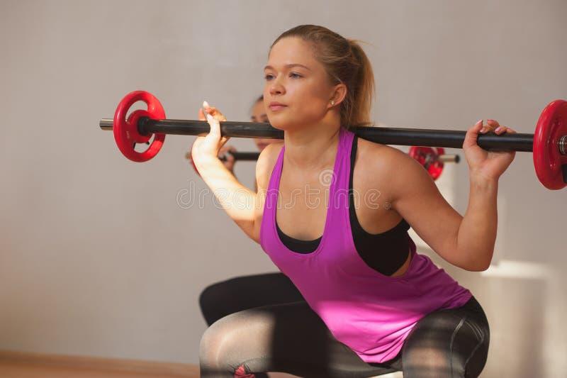 Groupe de jeunes femmes convenables s'exerçant avec des barbells image stock
