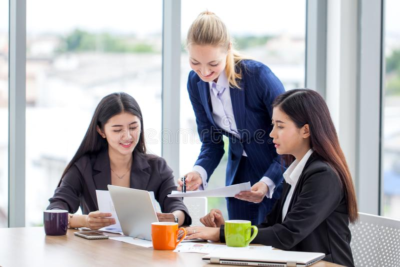 Groupe de jeunes femmes d'affaires se réunissant dans la chambre de bureau Travail de femmes photographie stock libre de droits