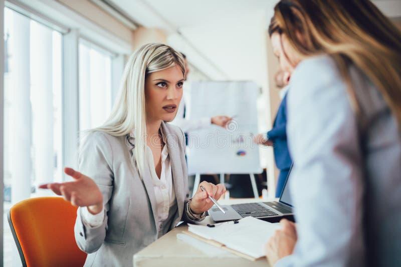 Groupe de jeunes femmes d'affaires travaillant et communiquant tout en se reposant au bureau ensemble photos stock