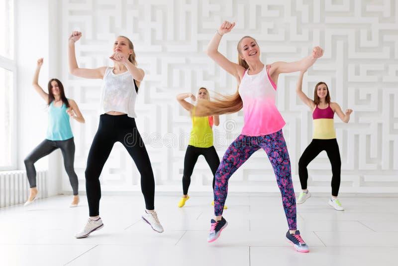 Groupe de jeunes femmes dansant avec des bras augmentés tout en ayant une classe de danse de forme physique images stock
