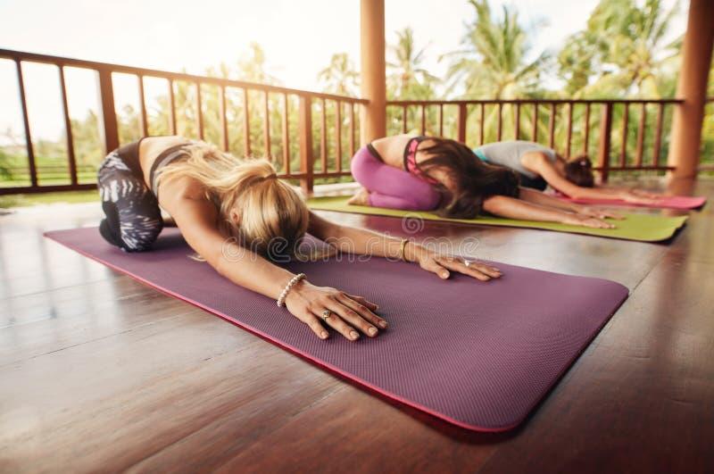 Groupe de jeunes femmes faisant le yoga de pose d'enfant images libres de droits