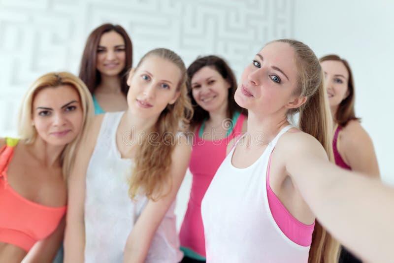 Groupe de jeunes femmes habillées dans les vêtements de sport prenant le selfie ensemble photos libres de droits