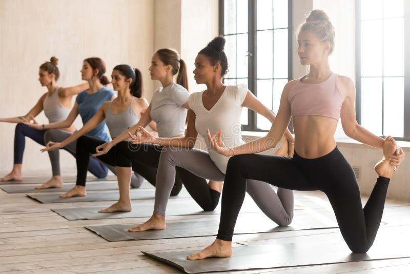 Groupe de jeunes femmes sportives pratiquant le yoga, faisant le cavalier de cheval images libres de droits