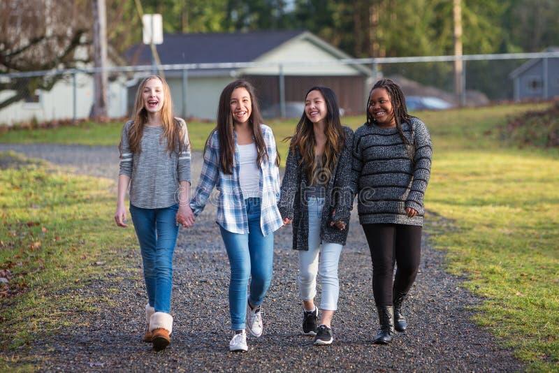 Groupe de jeunes filles tenant des mains et riant tout en marchant dessus images libres de droits