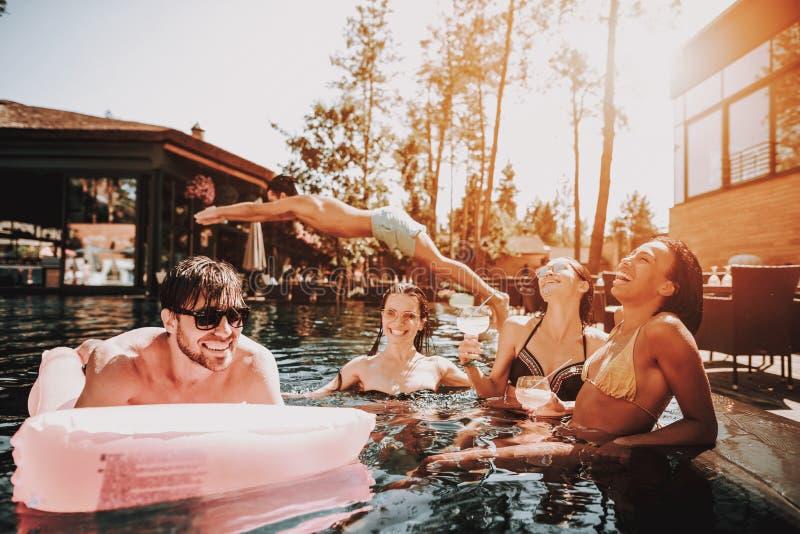 Groupe de jeunes heureux nageant dans la piscine photographie stock