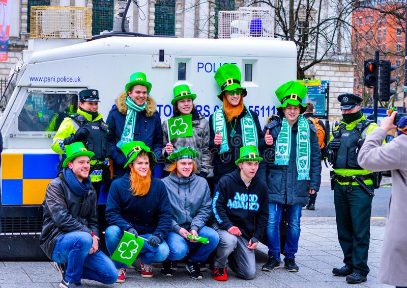 Groupe de jeunes hommes avec les chapeaux verts prenant la photo avec la police à Belfast au jour du ` s de St Patrick images stock