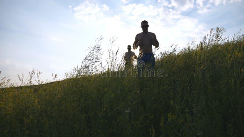 Groupe de jeunes hommes courant en bas de la colline verte au-dessus du ciel bleu avec la fusée du soleil au fond Les athlètes ma photographie stock