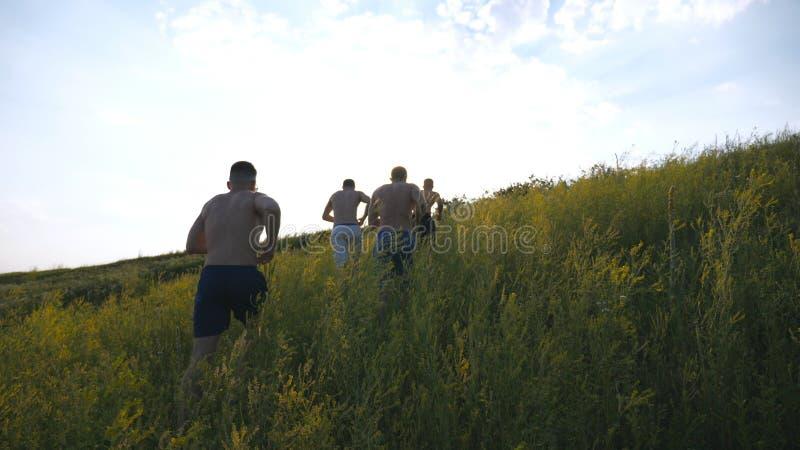 Groupe de jeunes hommes courant la colline verte au-dessus du ciel bleu avec la fusée du soleil au fond Les athlètes masculins pu photos libres de droits