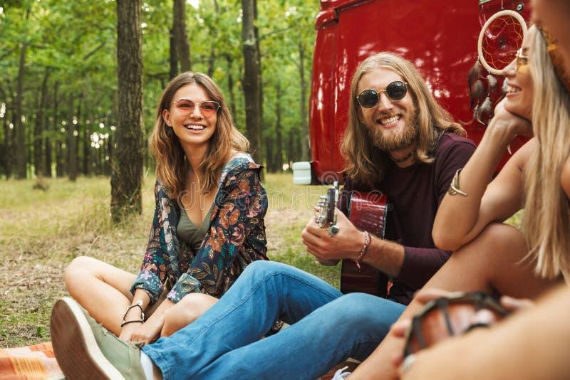 Groupe de jeunes hommes et de femmes de hippies riant, et presque s'asseyant images libres de droits