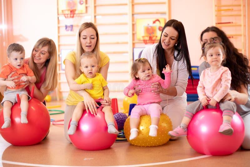 Groupe de jeunes mamans et leurs de bébés faisant des exercices de yoga sur les boules gymnastiques au gymnase de forme physique photo stock