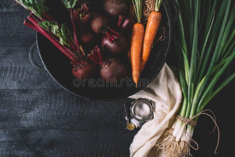 Groupe de jeunes oignons verts, betteraves, carottes et basilic sur un fond noir de vieux vintage de conseils en bois, légume fra photos stock