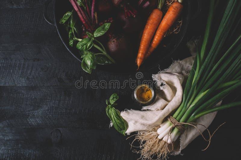 Groupe de jeunes oignons verts, betteraves, carottes et basilic sur un fond noir de vieux vintage de conseils en bois, légume fra images libres de droits